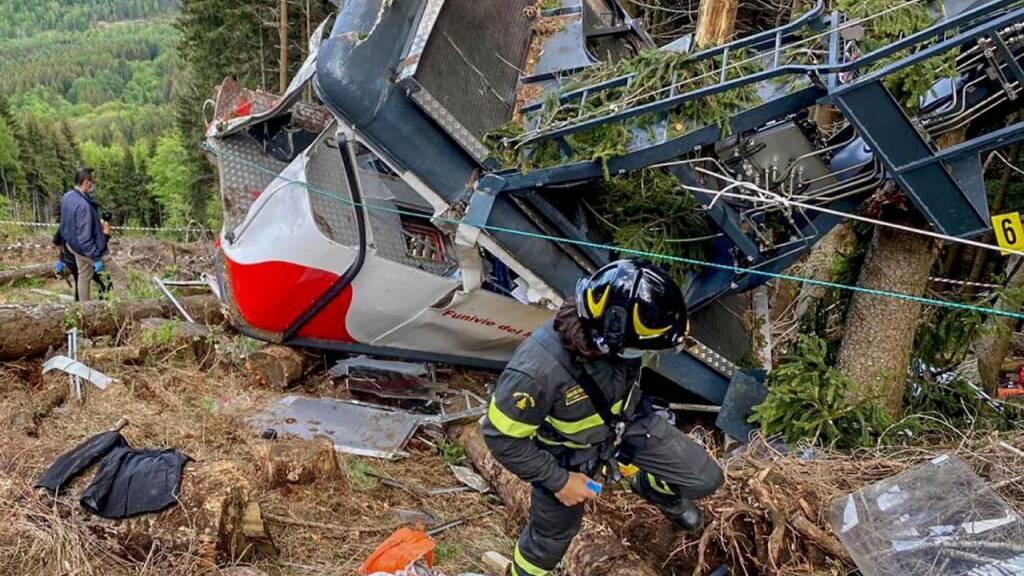 Rettungskräfte arbeiten am Wrack einer abgestürzten Gondel, die in einem Waldstück liegt. Nach dem Seilbahnunglück in Italien soll die Unglücksgondel mit einem Hubschrauber abtransportiert werden.