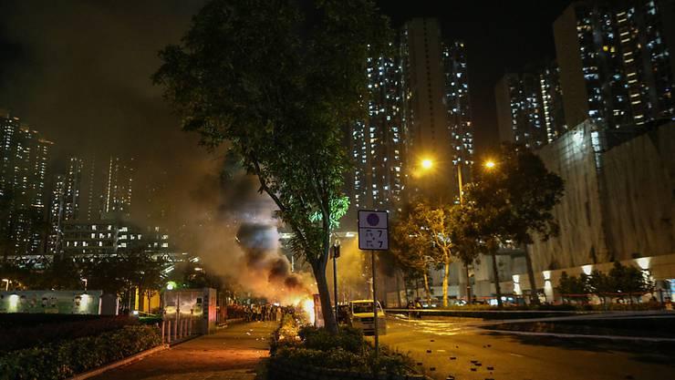 Demonstranten in Hongkong haben erneut Strassen blockiert und brennende Barrikaden errichtet.