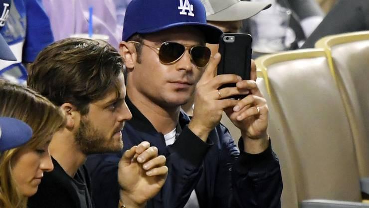 Zac Efron (mit Handy) findet, Comedy sei nicht seine Stärke. Er möchte seriöse Rollen übernehmen (Archiv)