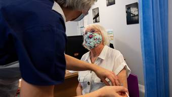 Die 84-jährige Maureen Hughes erhält den Pfizer/Biontech-Impfstoff in der Feldon Lane Surgery. Foto: Jacob King/PA Wire/dpa