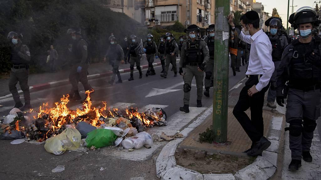 Polizisten gehen während einer Demonstration von ultraorthodoxen Juden auf einer Straße an brennendem Müll vorbei. Foto: Oded Balilty/AP/dpa