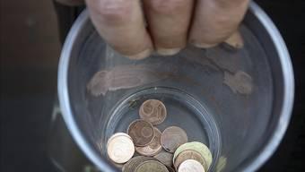 Strassenmusiker hält einen Becher mit Kleingeld. (Symbolbild)