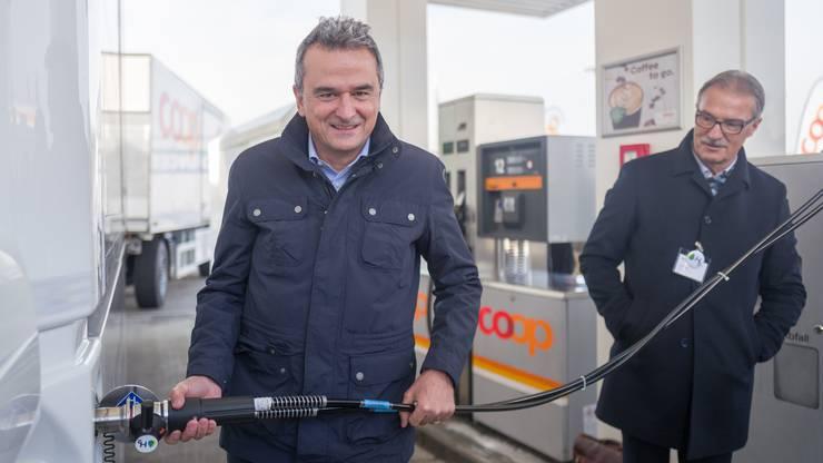 Joos Sutter (Vorsitzender der Geschäftsleitung Coop) tankt den Wasserstofflastwagen, während Leo Ebneter (Leiter Direktion Logistik der Coop Genossenschaft) ihn beobachtet.