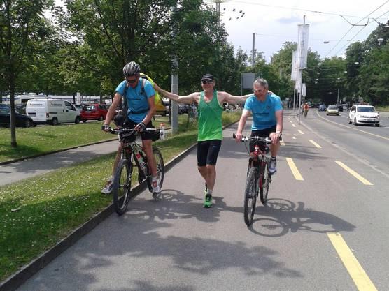 Schmid wird von zwei Velofahrern begleitet.