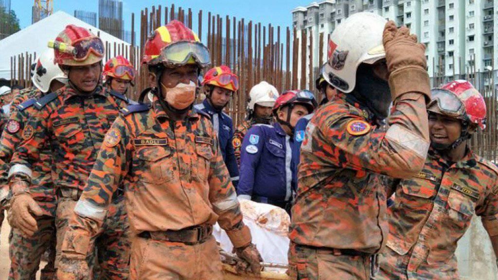Rettungskräfte tragen ein Opfer des Erdrutsches in Tanjung Bungah auf der malaysischen Insel Penang davon.
