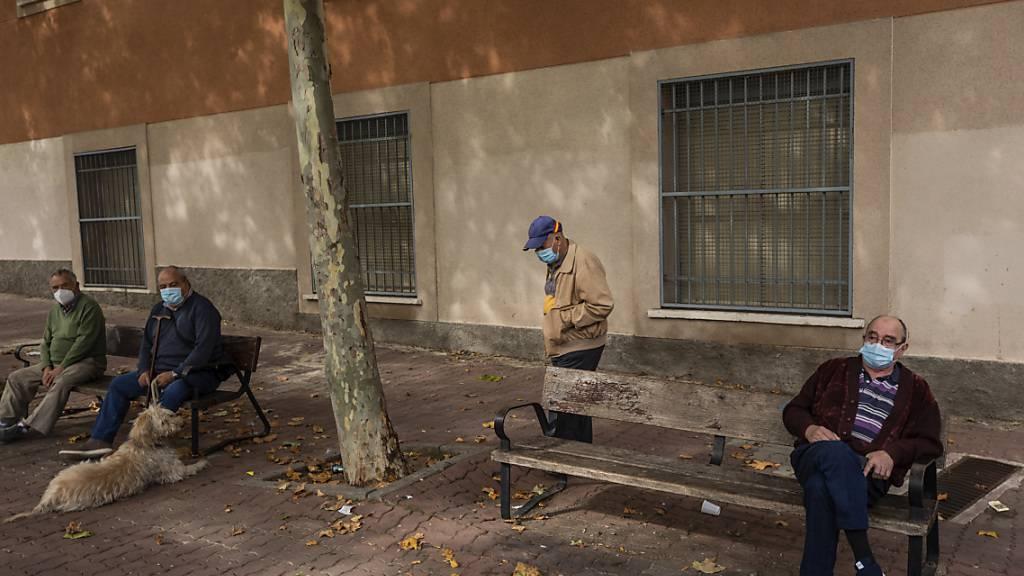 Ältere Menschen sitzen in einem Park in Vallecas, einem ärmeren Madrider Viertel, das teilweise abgeriegelt ist. Foto: Bernat Armangue/AP/dpa
