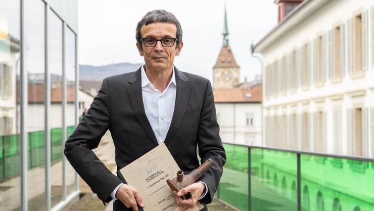 Peter Hossli vor der Aargauer Kantonsbibliothek mit einer Gerichtsakte und der originalen Tatwaffe, dem Fuss eines Wagenhebers.