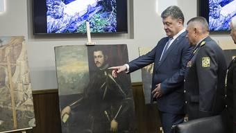 Der ukrainische Präsident Poroschenko begutachtet die sichergestellten Bilder.