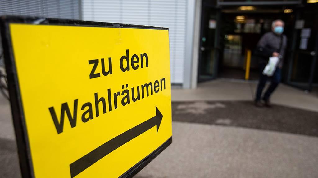 Ein Schild mit der Aufschrift «Zu den Wahlräumen» steht vor dem Wahllokal im deutsch-französischen Gymnasium in Freiburg, während im Hintergrund ein Mann das Wahllokal verlässt. Am heutigen Tag sind die Bürgerinnen und Bürgerinnen in Baden-Württemberg zur Wahl eines neuen Landtages aufgerufen. Foto: Philipp von Ditfurth/dpa