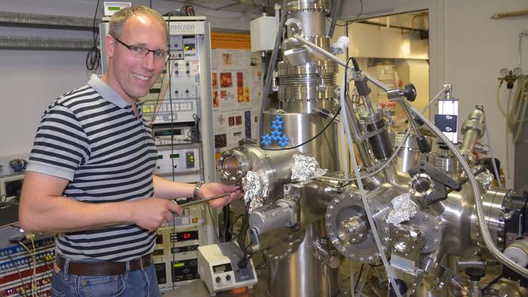 Physiker Thilo Glatzel zeigt ein Modell des Basler Molekular-Autos. Die Rennstrecke befindet sich im Innern des Rastertunnelmikroskops.