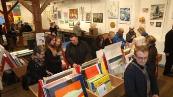 Zahlreiche Besucher stöbern am diesjährigen Kunst-Supermarkt in den Kisten mit unzähligen Kunstwerken.
