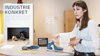 Kuratorin Flavia Muscionico am «Fliessband», auf dem die Geschichten von acht Aargauer Unternehmen erzählt werden. Die kleinen Besucher können Roboter programmieren.