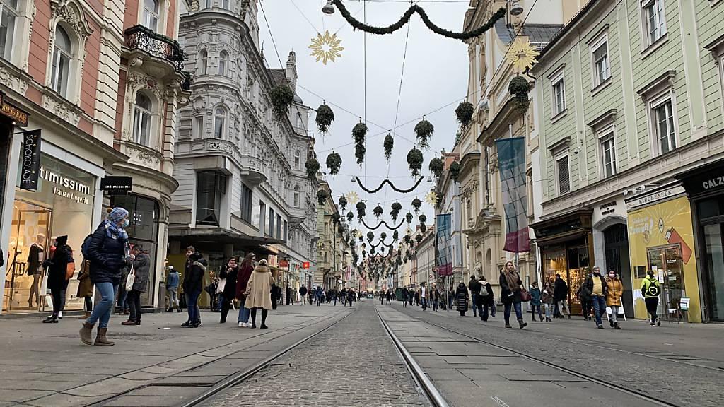 ARCHIV - Menschen mit Mund-Nasen-Schutz gehen in der Innenstadt von Graz an Geschäften vorbei. (Archivbild) Foto: Ingrid Kornberger/APA/dpa