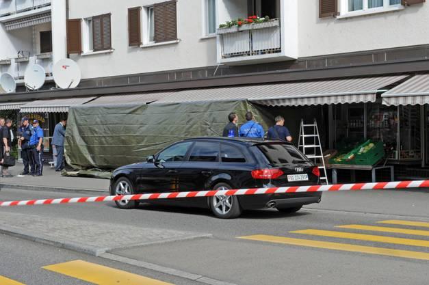Die Polizei sperrt den Tatort mit Plachen ab.