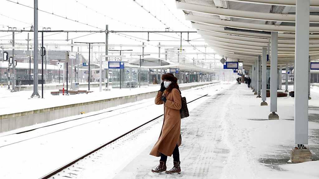 Eine Frau wartet auf dem Bahnsteig von Zwolle auf dem Zug. Schnee und Glätte behindern weiter das öffentliche Leben in den Niederlanden. Foto: Vincent Jannink/ANP/dpa