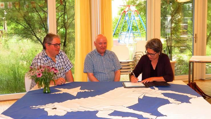 Manfred Ingold (Präsident Musikgesellschaft, links), Manfred Lehmann (Dirigent) und Christine Stebler (Gemeinderätin) unterzeichnen die Vereinbarung unter Beobachtung des Gesamtgemeinderates.