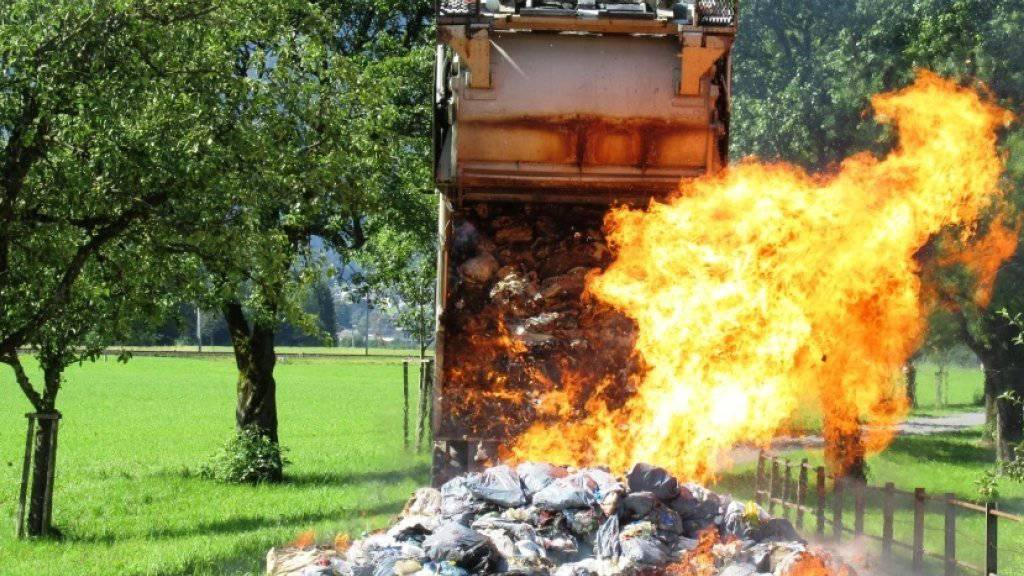 Hier brennen fünf Tonnen Abfall: Um den Kehrrichtwagen zu retten, kippten die Müllmänner den brennenden Abfall auf eine Landstrasse im glarnerischen Näfels.