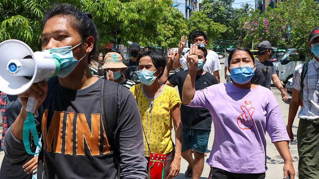 Menschen zeigen bei einer Demonstration den Drei-Finger-Gruß als Zeichen des Widerstands. Foto: --/AP/dpa