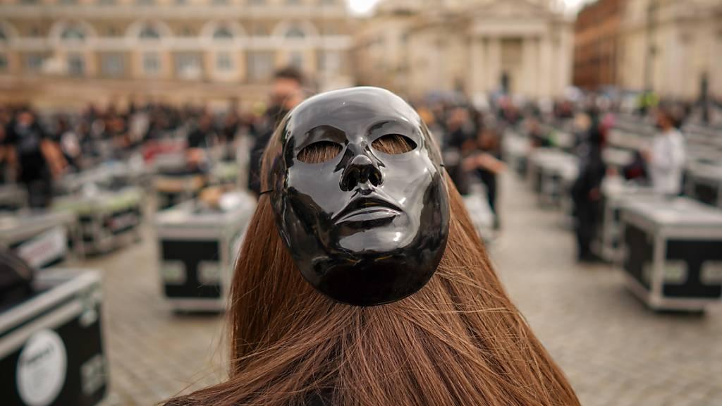 Beschäftigte der Unterhaltungsindustrie versammeln sich auf der Piazza del Popolo, um gegen die Wirtschaftspolitik der italienischen Regierung während der Corona-Panemie zu protestieren und die Wiedereröffnung ihrer Geschäfte zu fordern. Foto: Andrew Medichini/AP/dpa