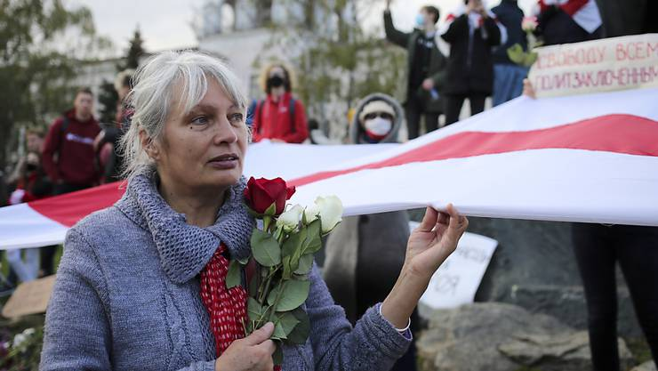 dpatopbilder - Eine Frau hält bei einer Demonstration Rosen und die historische weiß-rot-weiße Fahne in der Hand. Tausende Menschen, darunter vor allem Senioren und Studenten, marschierten am Montag durch die Hauptstadt. Foto: -/AP/dpa