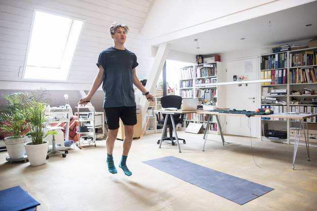 Schweizer Snowboarder David Hablützel trainiert zu Hause im Wohnzimmer.