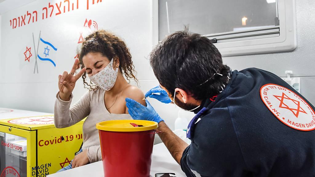 HANDOUT - Eine junge Frau wird in Israel in einem mobilen Impf-Bus geimpft. Foto: Kfir Sivan/Tel Aviv-Yafo Municipality/dpa - ACHTUNG: Nur zur redaktionellen Verwendung im Zusammenhang mit der aktuellen Berichterstattung und nur mit vollständiger Nennung des vorstehenden Credits