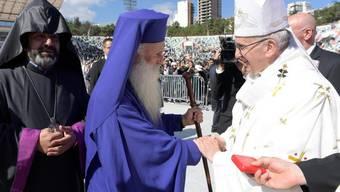Papst Franziskus begrüsst orthodoxe Kleriker, die an seiner Messe im Micheil-Meschi-Stadion von Tiflis teilnahmen.