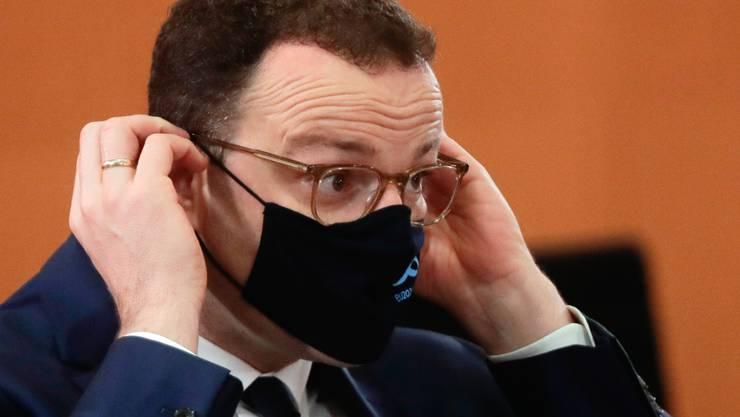 Jens Spahn (CDU), Bundesgesundheitsminister, richtet seinen Mund-Nasen-Schutz während einer Sitzung des Bundeskabinetts im Kanzleramt. Spahn ist positiv auf das Coronavirus getestet worden. Das teilte das Gesundheitsministerium am Mittwoch (21.10.2020) in Berlin mit. Foto: Markus Schreiber/AP-Pool/dpa