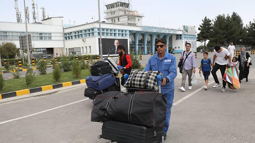 Passagiere gehen zum Abflugterminal des internationalen Flughafens Hamid Karzai in Kabul. Die militant-islamistischen Taliban setzen ihren Vormarsch in Afghanistan fort und rücken dabei immer näher an die Hauptstadt Kabul heran. Foto: Rahmat Gul/AP/dpa