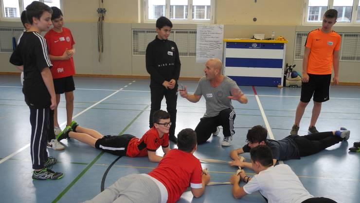 Kursleiter Alex Michel bespricht mit seinen Jungs nach dem Spiel, wer unfair gehandelt hat und was sie in der nächsten Runde verbessern können