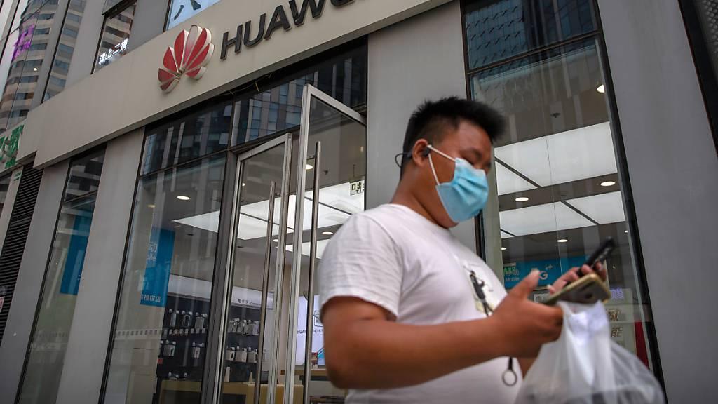 ARCHIV - Ein Mann mit Gesichtsmaske schaut auf sein Smartphone, als er an einem Huawei-Laden in Peking vorbeigeht. Der chinesische Technologiekonzern Huawei soll nun endgültig nicht am Ausbau des superschnellen 5G-Mobilfunknetzes in Großbritannien beteiligt werden. Foto: Mark Schiefelbein/AP/dpa