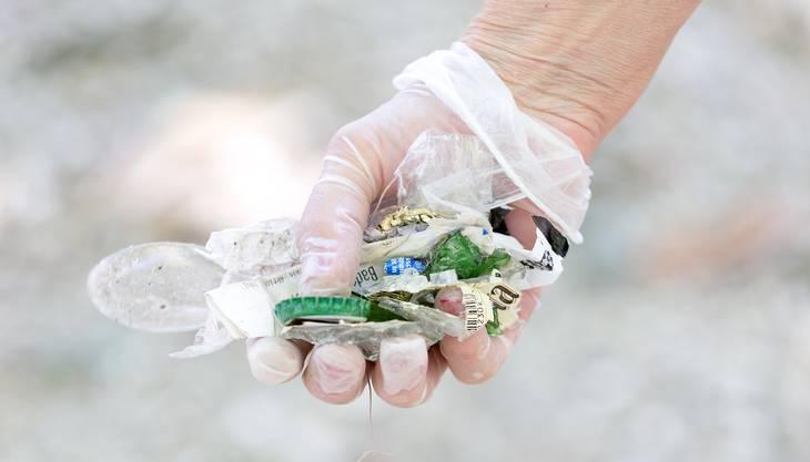 Mit Handschuhen aus dem Baumarkt hebt Annemarie Martin den Abfall auf.