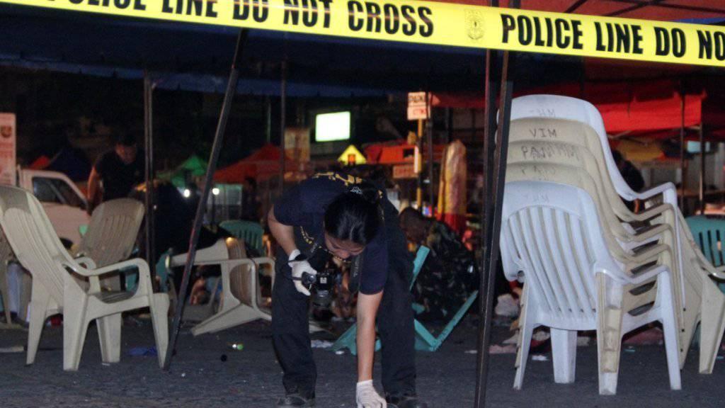 Eine Polizistin bei der Spurenaufnahme nach der Bombenexplosion in Davao auf der philippinischen Insel Mindanao.