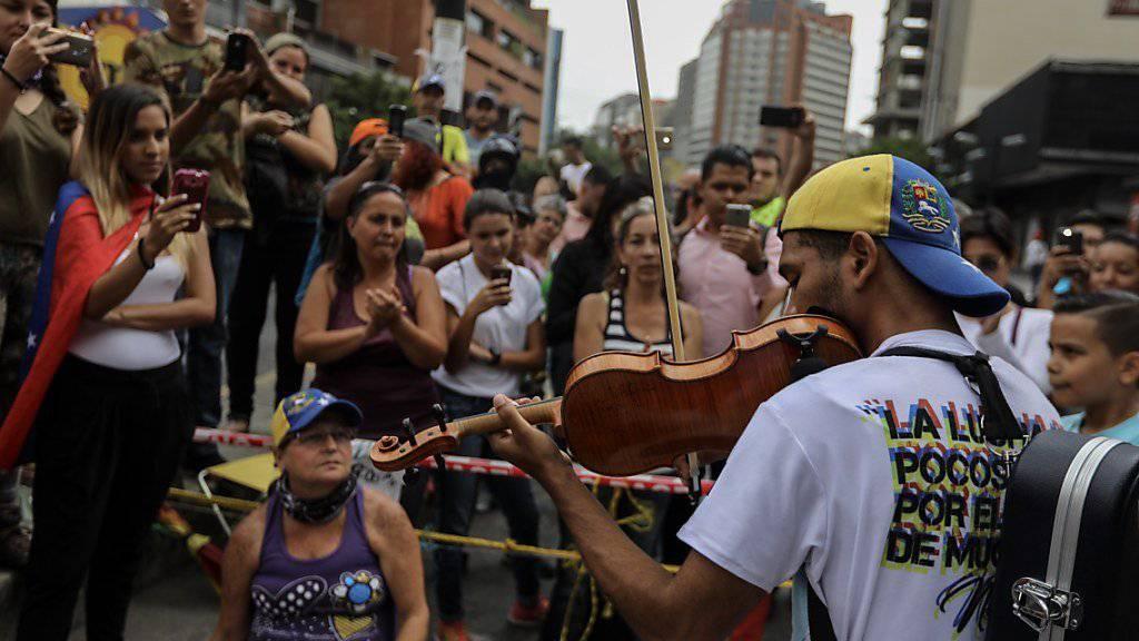 Der Violinspieler Willy Arteaga wird bei Protesten in Venezuelas Hauptstadt Caracas durch Tränengas verletzt. (Archivbild)