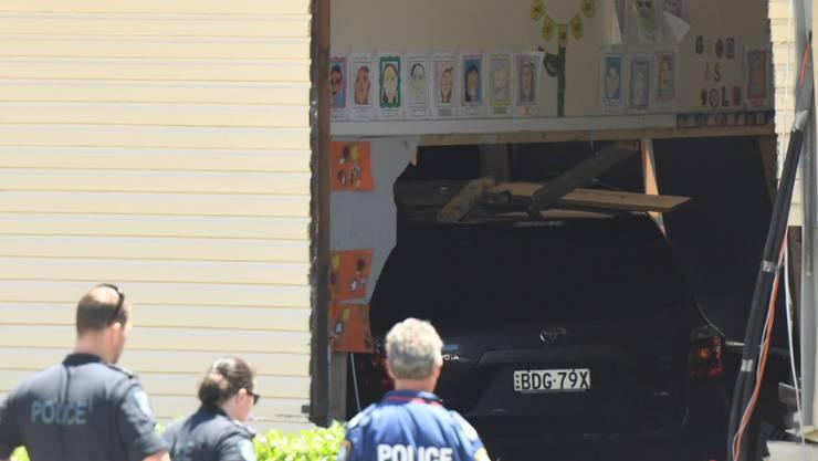 Polizisten und Sanitäter am Unfallort in Sydney. Eine Frau raste mit dem Auto in ein Schulgebäude. Zwei Kinder starben, zwanzig wurden verletzt.  Die Polizei geht von einem tragischen Unfall aus.