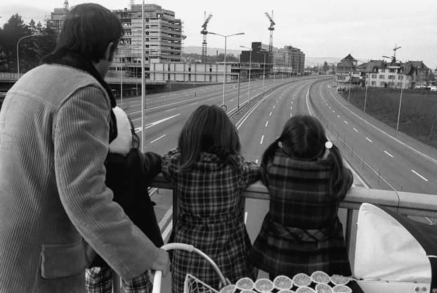Auf dem Höhepunkt der Erdölkrise wurden 1973 in der Schweiz einige autofreie Sonntage eingeführt, was diesen Passanten den seltenen Anblick einer leeren Autobahn bescherte.