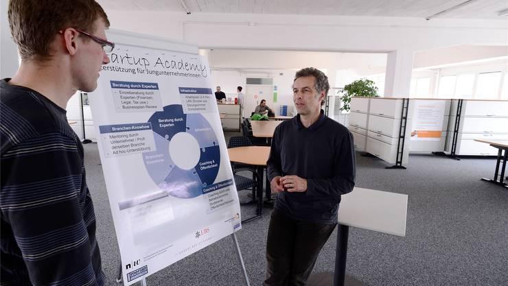 Florian Blumer (rechts) bespricht sich mit einem Jungunternehmer, im Hintergrund die Büroräume der «Startup Academy».