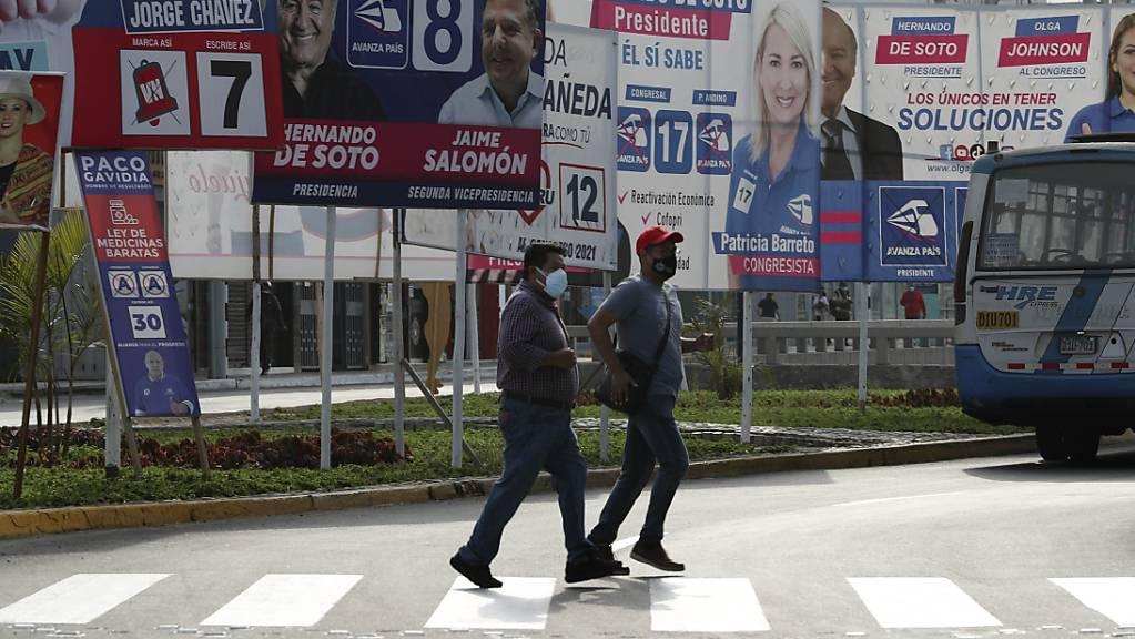 Menschen mit Mund-Nasen-Bedeckung überqueren eine Straße, an der Wahlplakate der Präsidentschaftskandidaten hängen. Foto: Martin Mejia/AP/dpa