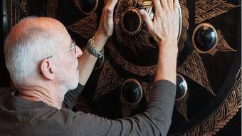 Wolfgang Rogg beim Anreiben mit den Händen über den Buckel des grossen thailändischen Gongs