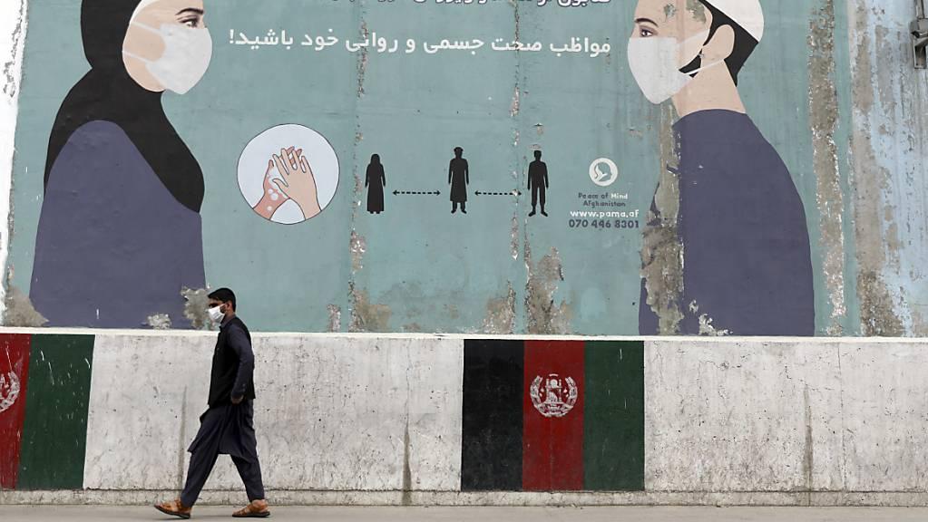 Ein Passant geht in der afghanischen Hauptstadt an einer bemalten Wand vorbei, auf der auf die coronabedingten Hygieneregeln hingewiesen wird. Zuletzt hat das Land mehr Coronatote binnen eines Tages verzeichnet als je zuvor.