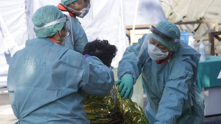 Krankenhaus-Personal kümmert sich um eine mit Corona-Virus infizierte Person in Norditalien.