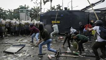 Demonstranten in Jakarta attackieren Polizisten mit Steinen und Stöcken.
