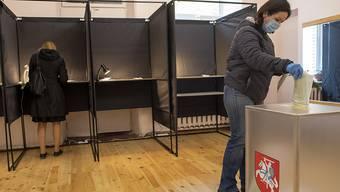 Eine Frau trägt einen Mund-Nasen-Schutz, während sie ihren Stimmzettel in eine Wahlurne wirft. Die Bürger in Litauen sind dazu aufgerufen, die 141 Sitze im Parlament zu erneuern. Foto: Mindaugas Kulbis/AP/dpa