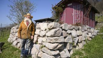 Ernst Werffeli steht vor der Natursteinmauer, die er in seinem Rebberg für Eidechsen baute. 1961 erstellte er am gleichen Ort zum ersten Mal eine Mauer für die Reptilien.