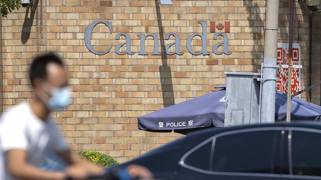 Ein Mann fährt auf einem Motorroller über eine Kreuzung in der Nähe der kanadischen Botschaft in Peking. Ein chinesisches Gericht hat vor dem Hintergrund der diplomatischen Spannungen zwischen China und Kanada das Todesurteil gegen einen kanadischen Drogenhändler bestätigt. Foto: Mark Schiefelbein/AP/dpa