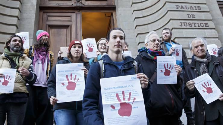 """Der angeklagte Klimaaktivist (Mitte vorne) wird beim Gang ans Gericht von anderen Mitgliedern der Bewegung """"Breakfree Schweiz"""" unterstützt. Auch der Stadtrat der Linken Alternative, Remy Pagani (rechts), bekundet seine Solidarität."""