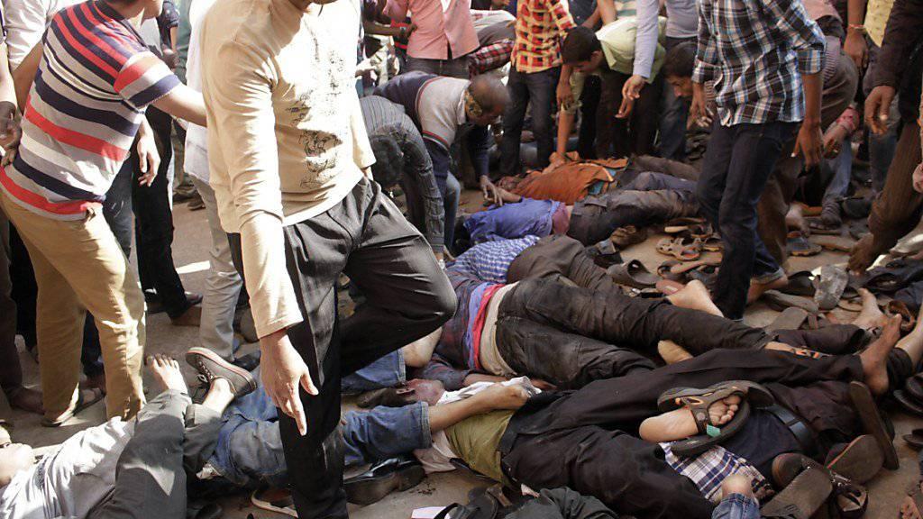 Teilnehmende einer Trauerfeier in Bangladesch suchen nach Angehörigen, die bei einer Massenpanik zu Tode getrampelt wurden.