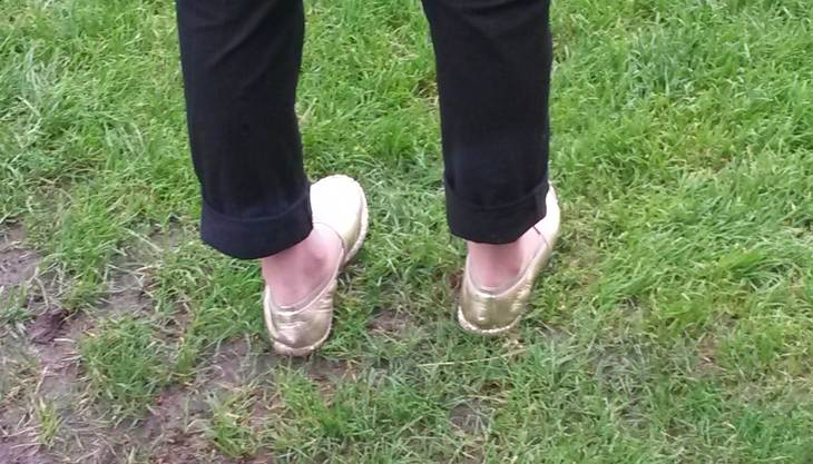 Goldene Ballerinas im matschigen Rasen? Diese japanische Journalistin vergisst für Kakitani ihr edles Schuhwerk.