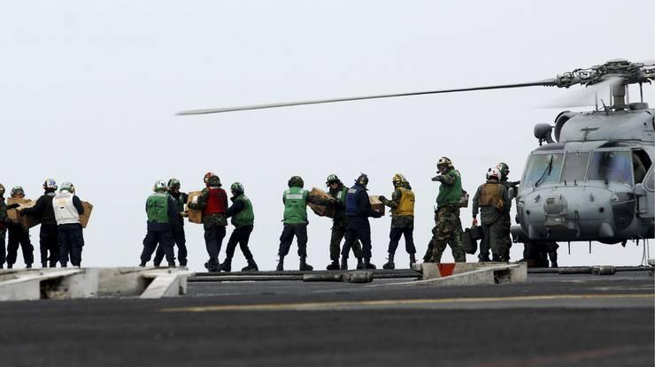 Angehörige der US Navy beladen einen Helikopter mit Hilfsgüter