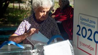 Eine Frau gibt ihre Stimme in einer Wahlurne in einem Wahllokal in Tambow ab. Foto: Lev Vlasov/SOPA Images via ZUMA Wire/dpa